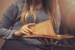 Kvinnan förlägger hennes armar på hennes varv och öppnar boken för att läsa royaltyfri bild