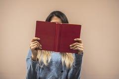 Kvinnan förlägger hennes armar på hennes varv och öppnar boken för att läsa royaltyfria foton