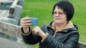 Kvinnan försöker att göra selfie och är jätteglad om den Rolig vuxen brunett med en smartphone i henne händer lager videofilmer