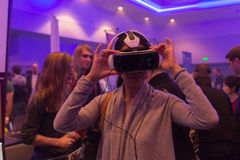 Kvinnan försöker hörlurar med mikrofon för det virtuell verklighetSamsung kugghjulet VR Arkivbilder