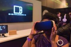 Kvinnan försöker virtuell verklighethörlurar med mikrofon Arkivbild