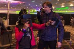Kvinnan försöker virtuell verklighethörlurar med mikrofon Royaltyfri Foto