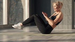 Kvinnan förstärker muskler av press med påfyllningen av övningar stock video