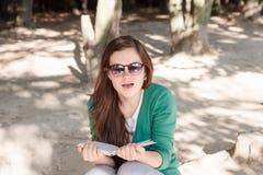 Kvinnan förvånade vid en fotograf, medan läsa en bok i PA fotografering för bildbyråer