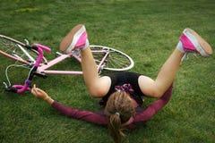 Kvinnan faller ner från cykeln arkivbild