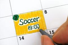 Kvinnan fingrar handstilpåminnelsefotboll i kalender Royaltyfri Bild