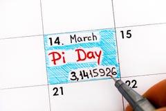 Kvinnan fingrar med dag för pi för pennhandstilpåminnelse i kalender arkivfoto