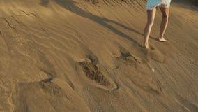Kvinnan flyr på dyn Fotspår på sanden Solnedgång på öken långsam rörelse arkivfilmer