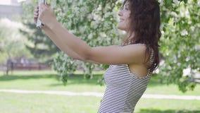 Kvinnan fotograferade sig på telefonen i parkera stock video