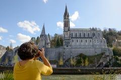 Kvinnan fotograferar domkyrkan i Lourdes, Frankrike Arkivfoto