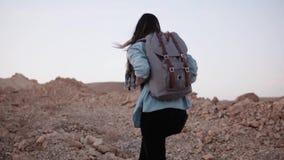 Kvinnan fotvandrar upp på en brant stenig kulle långsam rörelse Den turist- flickan klättrar berget med stora stenar Hård väg til arkivfilmer