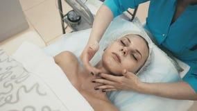 Kvinnan från brunnsortsalongen masserar försiktigt halsen av en ung attraktiv flicka lager videofilmer