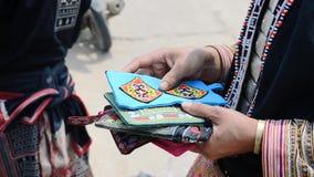 Kvinnan från stammen i Sapa (svarta Hmong) visar handgjort lager videofilmer