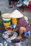 Kvinnan förbereder havs- till salu på marknadsgatan Arkivfoton