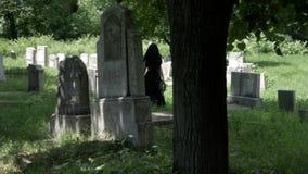 Kvinnan fyllde med sorgsenhet som ser från borttappad älskad grav som går i en kyrkogård lager videofilmer