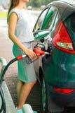 Kvinnan fyller bensin in i bilen på en bensinstation Arkivbilder