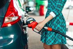 Kvinnan fyller bensin in i bilen på en bensinstation Royaltyfri Fotografi