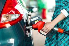 Kvinnan fyller bensin in i bilen på en bensinstation Royaltyfri Bild