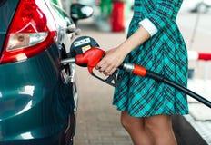 Kvinnan fyller bensin in i bilen på en bensinstation Royaltyfria Foton