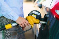 Kvinnan fyller bensin in i bilen på en bensinstation Arkivfoto