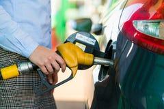 Kvinnan fyller bensin in i bilen på en bensinstation Royaltyfri Foto