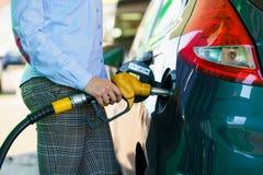 Kvinnan fyller bensin in i bilen på en bensinstation Arkivfoton