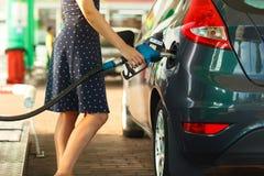 Kvinnan fyller bensin in i hennes bil Royaltyfria Bilder