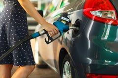 Kvinnan fyller bensin in i hennes bil Royaltyfri Fotografi