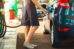 Kvinnan fyller bensin in i hennes bil Royaltyfri Bild