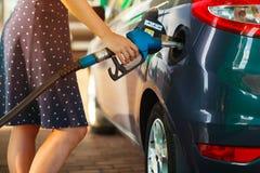 Kvinnan fyller bensin in i hennes bil Arkivfoton