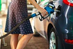 Kvinnan fyller bensin in i hennes bil Fotografering för Bildbyråer