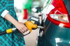 Kvinnan fyller bensin in i hennes bil på en bensinstation Royaltyfri Bild