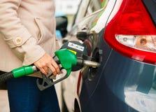 Kvinnan fyller bensin in i hennes bil på en bensinstation Royaltyfria Foton