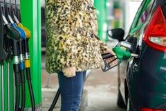 Kvinnan fyller bensin in i hennes bil på en bensinstation i vinter Arkivbild