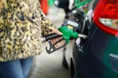Kvinnan fyller bensin in i hennes bil på en bensinstation i vinter Fotografering för Bildbyråer