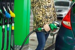 Kvinnan fyller bensin in i hennes bil på en bensinstation i vinter Arkivfoton