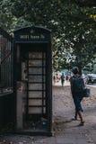 Kvinnan går den svarta telefonasken för forntiden på den Euston vägen i London, UK royaltyfri bild