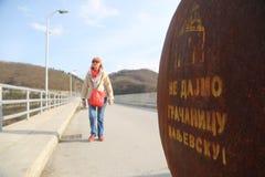Kvinnan går förbi grafiten översvämningskloster Valjevska Gracanica i sjön arkivbilder