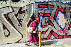 Kvinnan går förbi grafittiväggen i Belleville, Paris, Frankrike Arkivbilder