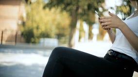 Kvinnan går i det defocused är går in i fokuszon sitter ner på bänkbruk som smartphonen läser text arkivfilmer