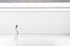 Kvinnan går i museumgalleri med den tomma väggen royaltyfria bilder