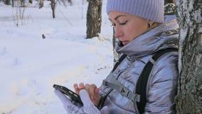 Kvinnan går i träna Handelsresanden fotograferas på telefonen i skogflicka gör selfie och meddelar med lager videofilmer