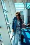Kvinnan går loppet med dräktfallet på flygplatsen Royaltyfria Foton
