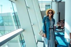 Kvinnan går loppet med dräktfallet på flygplatsen Royaltyfri Foto