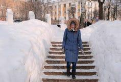Kvinnan går ner på en snöig stege, trappuppgång Vintern parkerar i staden under dagen i snöig väder med fallande snö royaltyfri bild
