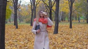 Kvinnan går på Autumn Park Holding en mapp eller en bärbar dator och att dricka kaffe arkivfilmer