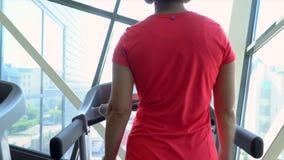 Kvinnan går på löparbanan Sportkvinnadreven på löparbanan isolated rear view white Ben stänger sig upp stock video