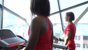Kvinnan går på löparbanan Sportkvinnadreven på löparbanan Sportkvinnan är förlovad med instruktören arkivfilmer