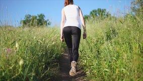Kvinnan går upp banan på en kulle som studerar naturen som en turist lager videofilmer