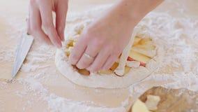 Kvinnan gör den nya äppelpajen i hennes kök arkivfilmer